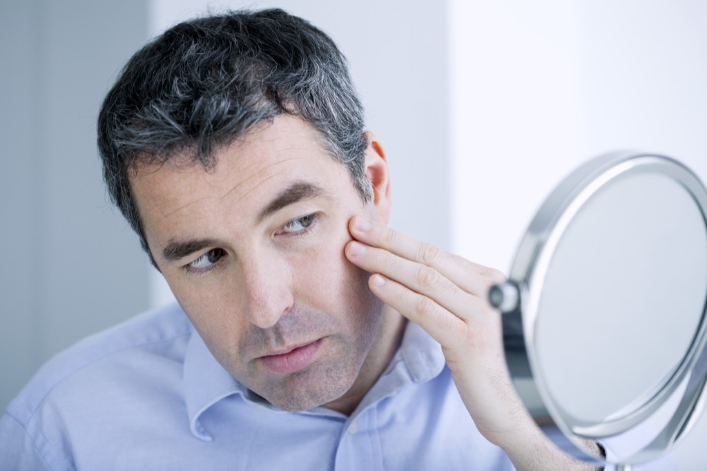 man looking at wrinkles in the mirror, ways your body changes after 40