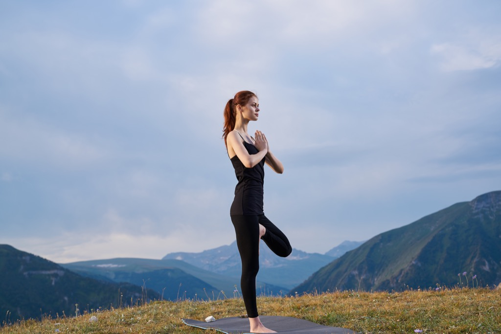 Beautiful woman doing yoga for better health and not getting sick at work