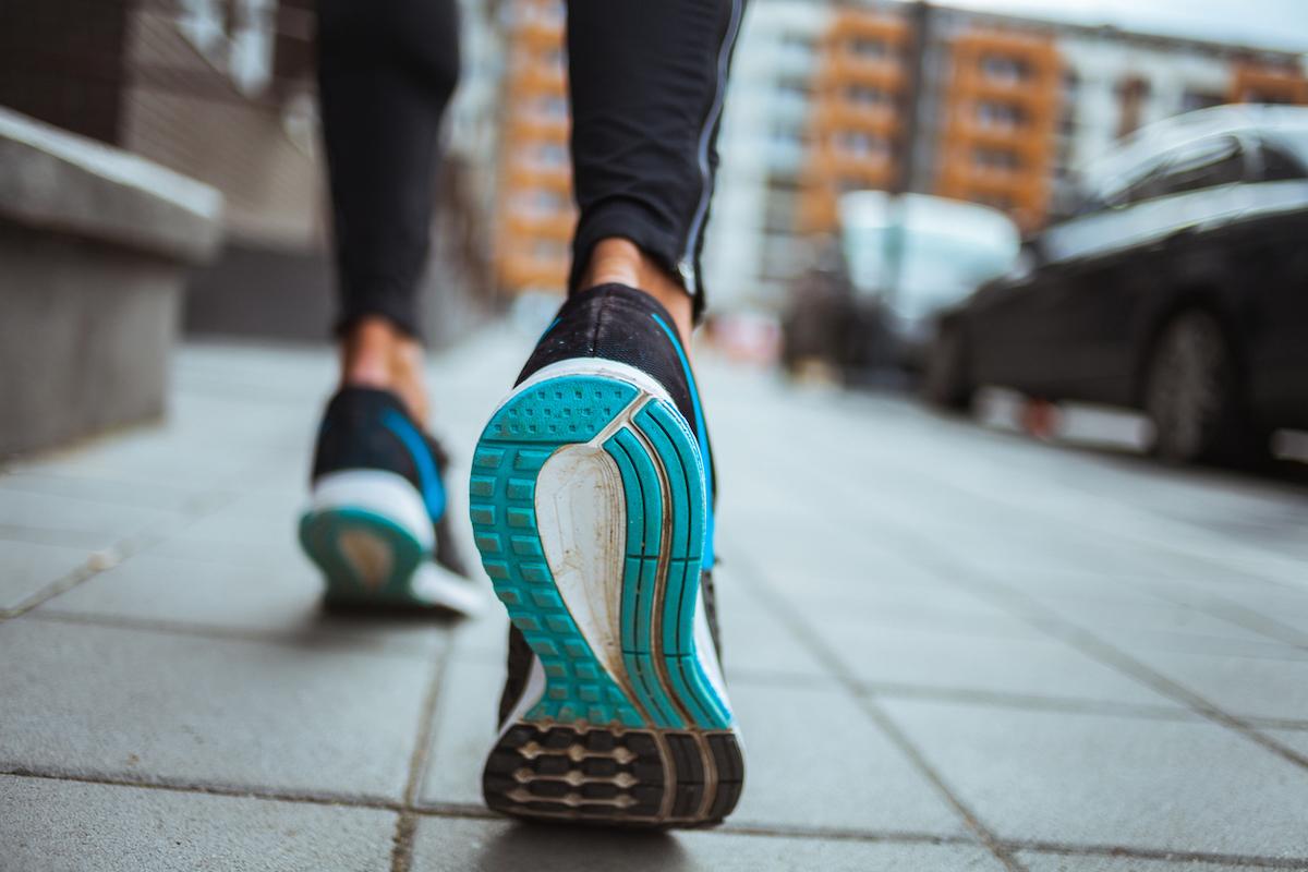 closeup shot of runner's shoes on sidewalk