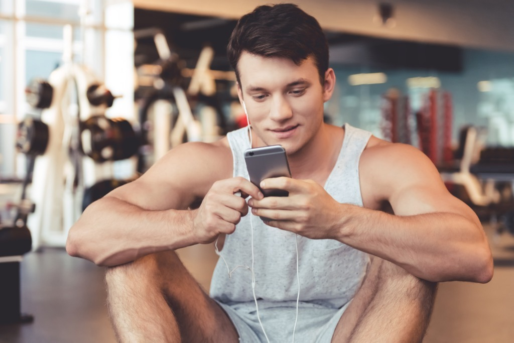 man listening to music at the gym, weight loss motivation