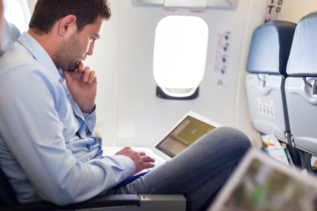 man working on laptop on airplane