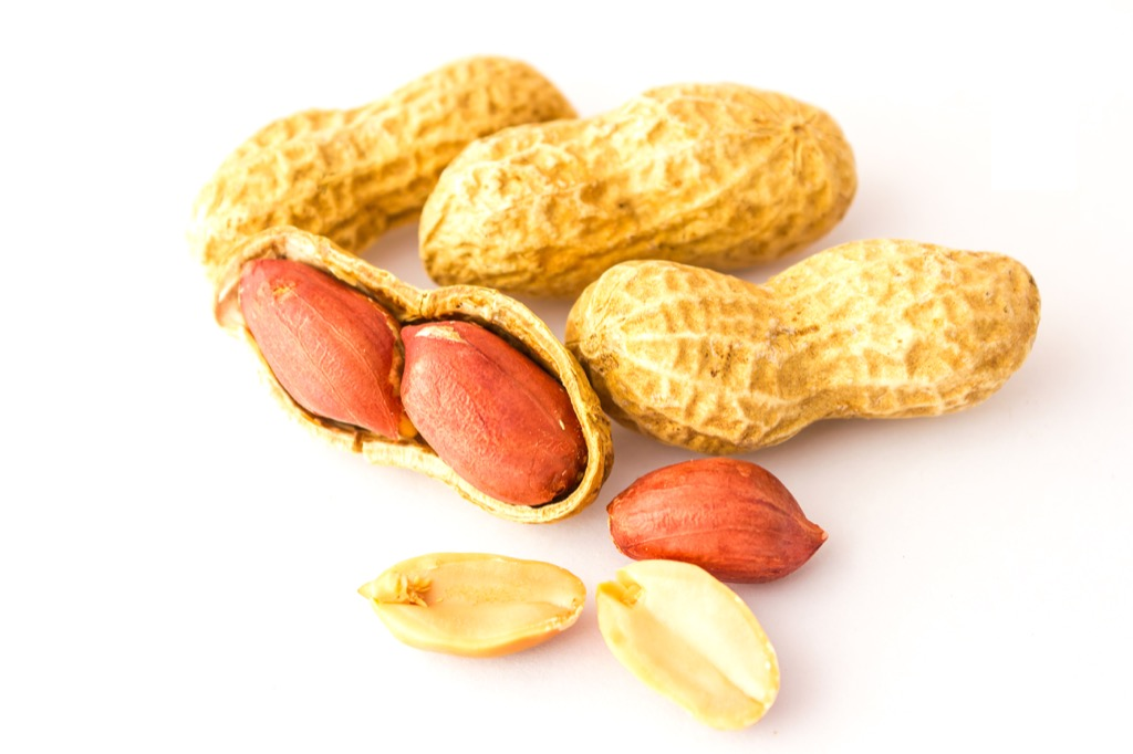 three peanuts on white background, one is partially cracked