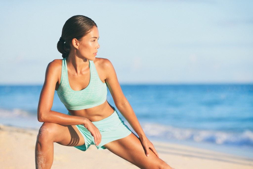 losing weight in your 40s woman stretching on a beach best body