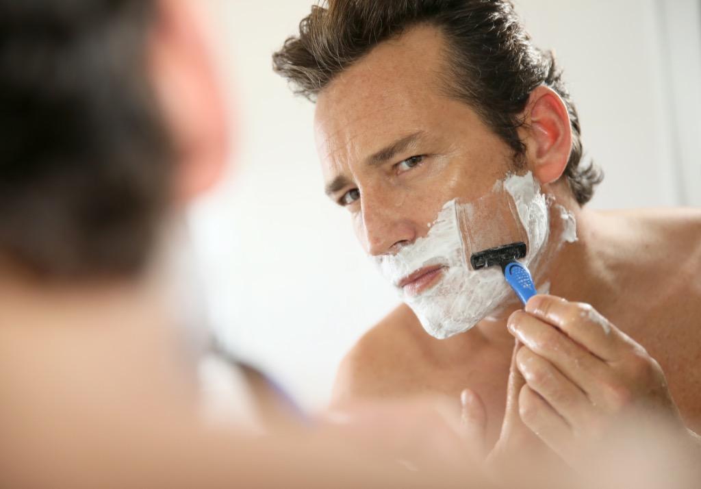 middle aged man shaving beard