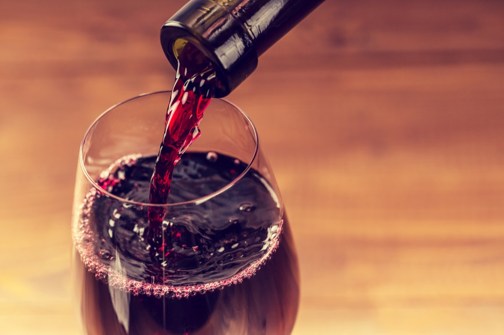 A glass of red wine being poured.