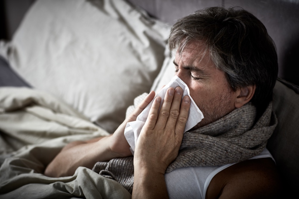 man sneezing in bed, ways your body changes after 40
