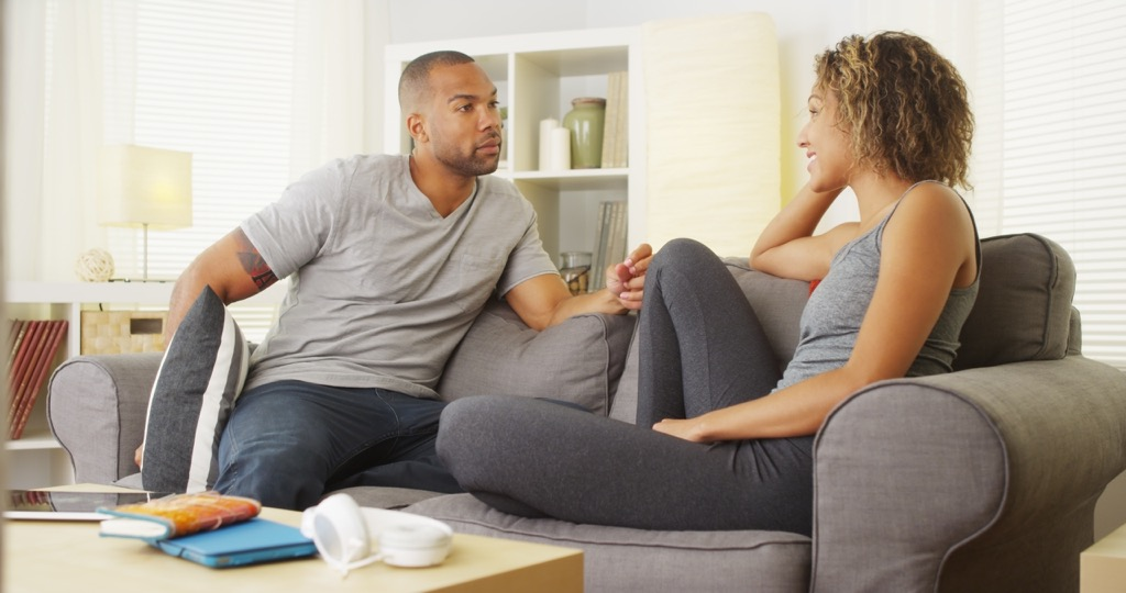 couple talking on the couch at home, open marriage