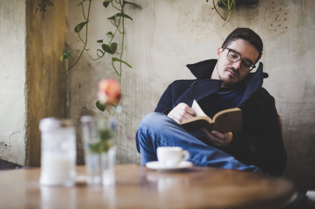 Man with glasses reading a book at a restaurant table, open marriage