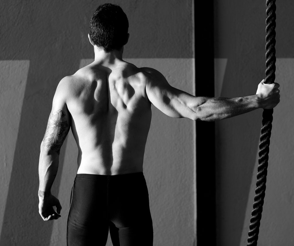 Muscular man at the gym holding a rope six-pack abs
