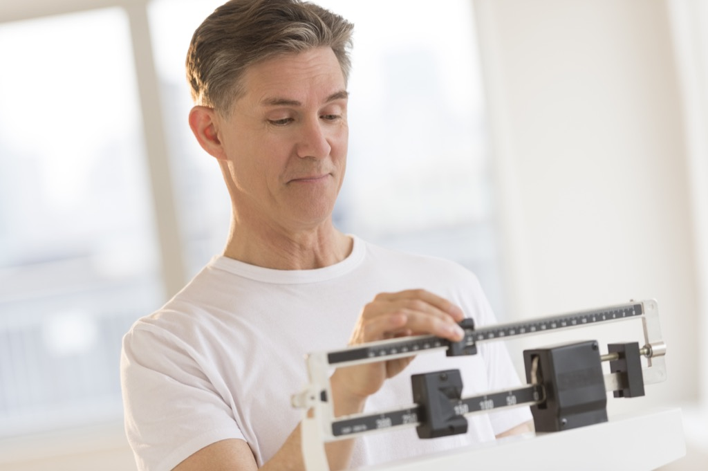 middle aged white man checks weight on scale