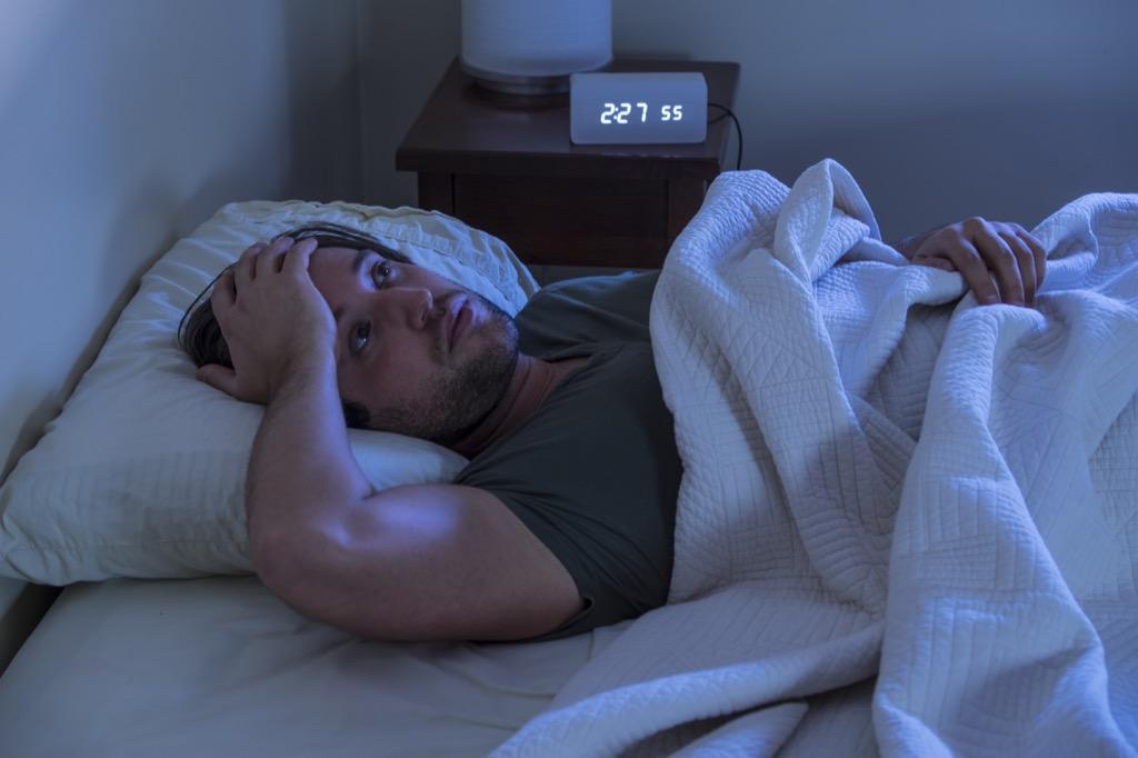 man awake in bed at 2 AM, subtle symptoms of serious disease