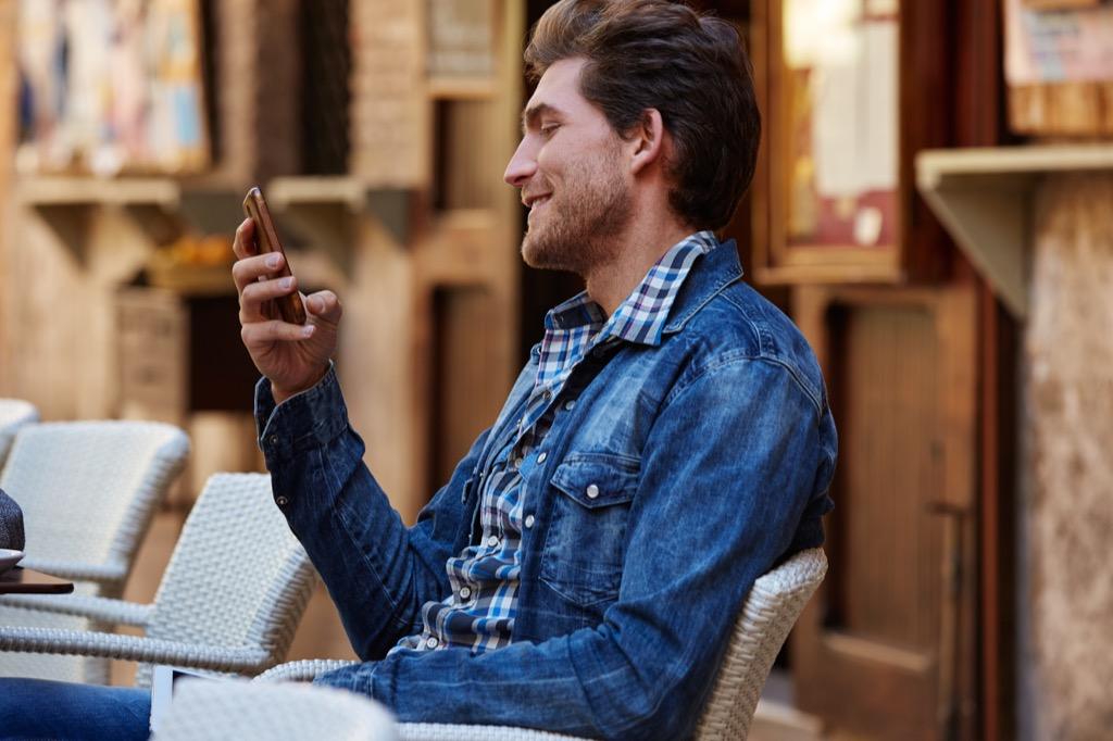 man at outside cafe on his phone, The best opening lines for online dating