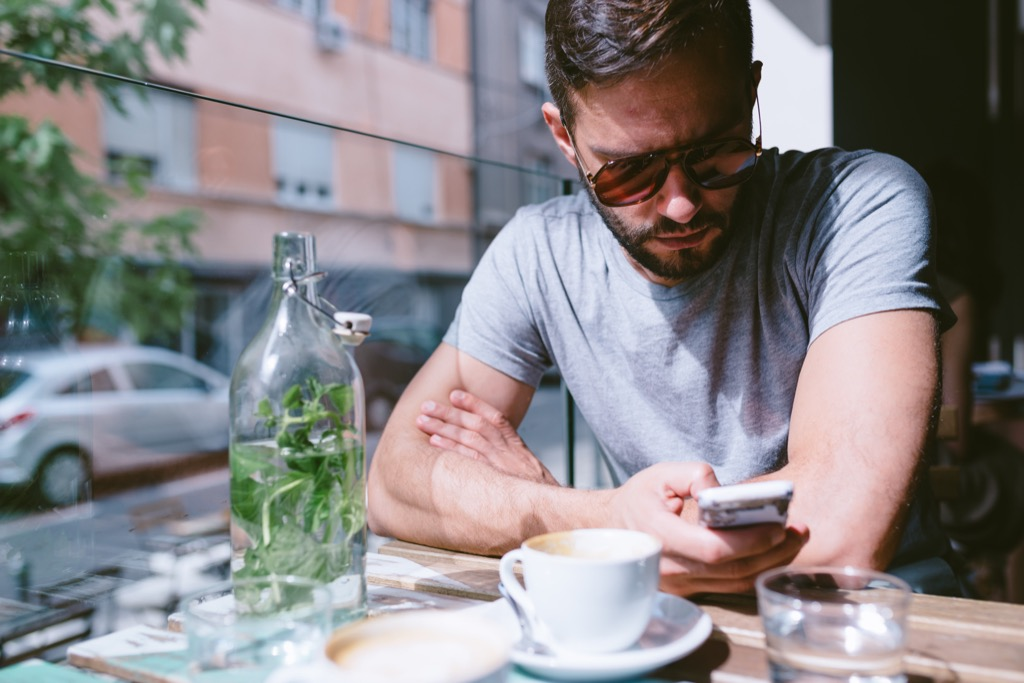 man on his phone at an outdoor cafe, The best opening lines for online dating