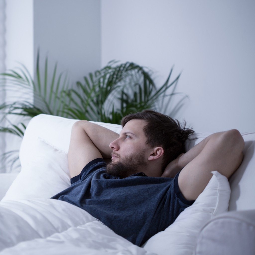 man laying in bed, ways your body changes after 40