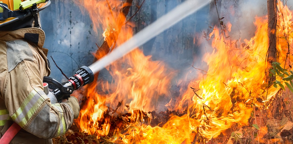 Fire fighter pouring water on fire