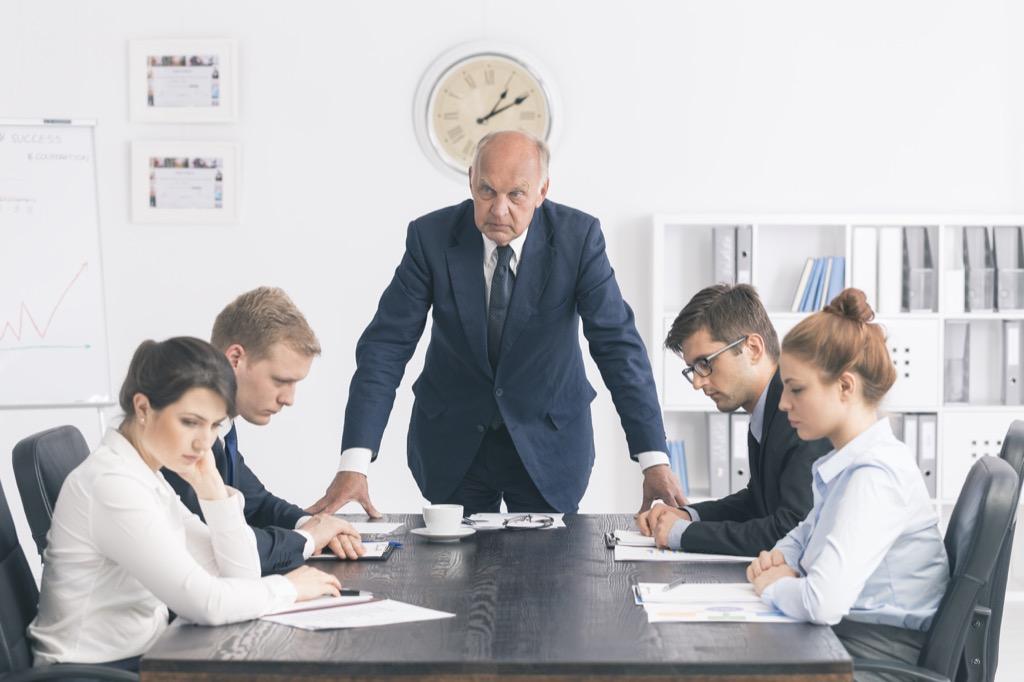 An angry, upset boss running a meeting.