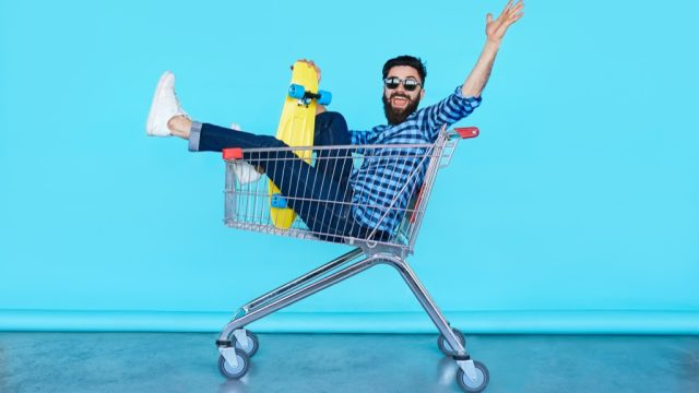 man in a shopping cart, carefree, putting himself at risk.