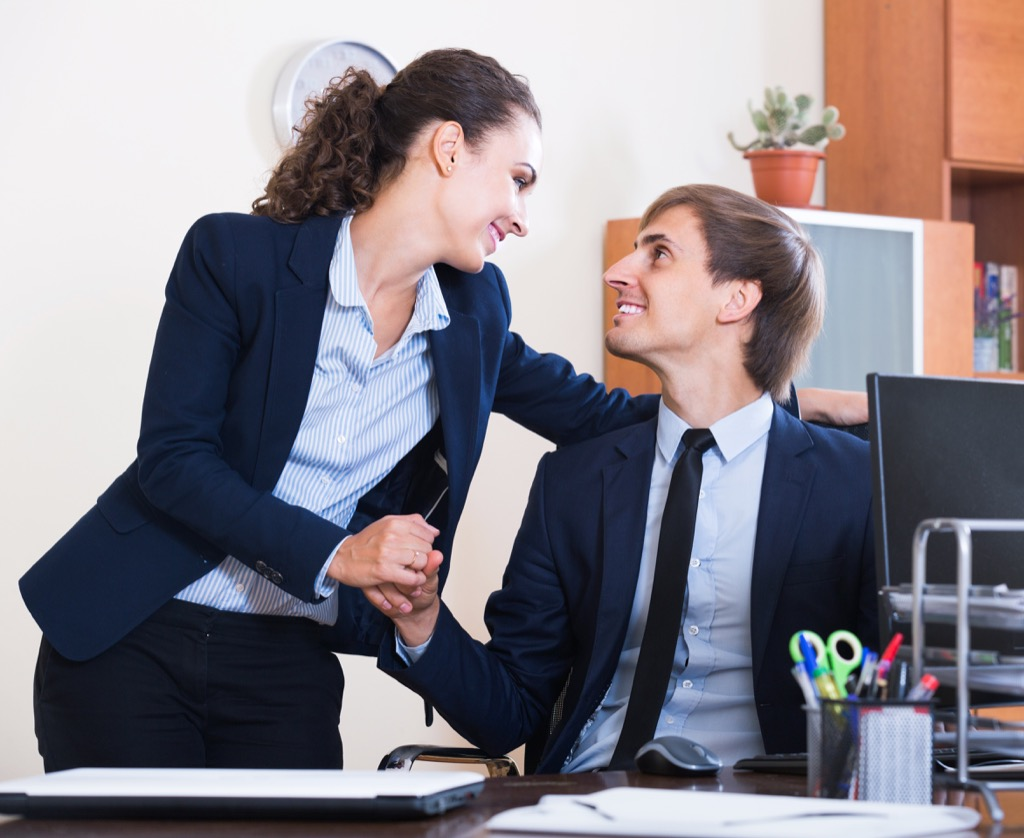 woman holding a man's hand at work, how to tell if a girl likes you