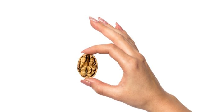 Woman holding a walnut, representing the prostate massage.