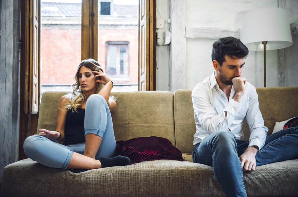 couple upset on a couch, signs your husband is cheating