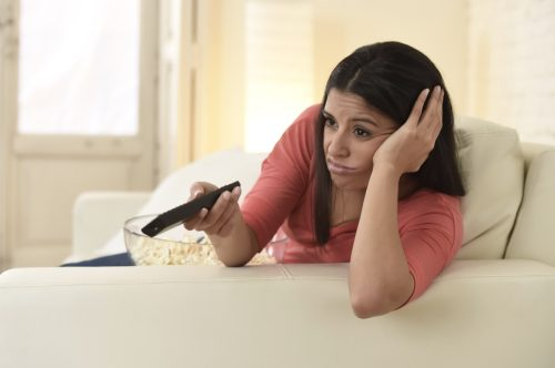 Woman watching TV and looking uninterested