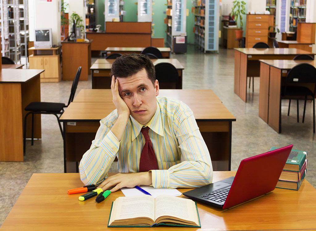 Bored man reading book college professor secrets