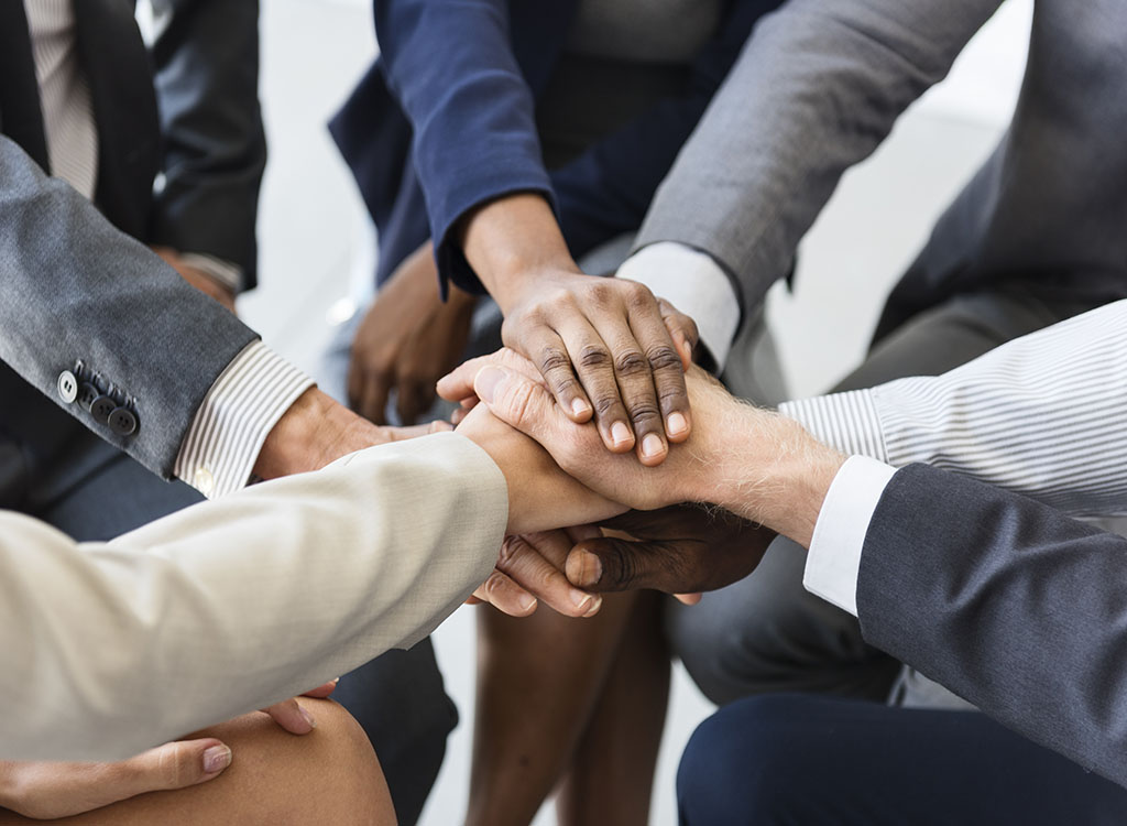 several hands touching in the middle of a circle