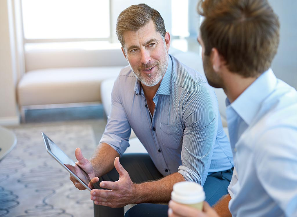older businessman talking to his younger colleague, annoying things people do