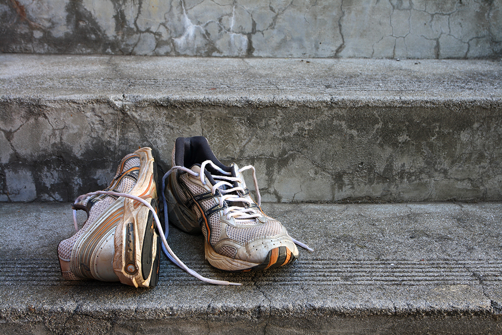 A pair of old running shoes on stairs