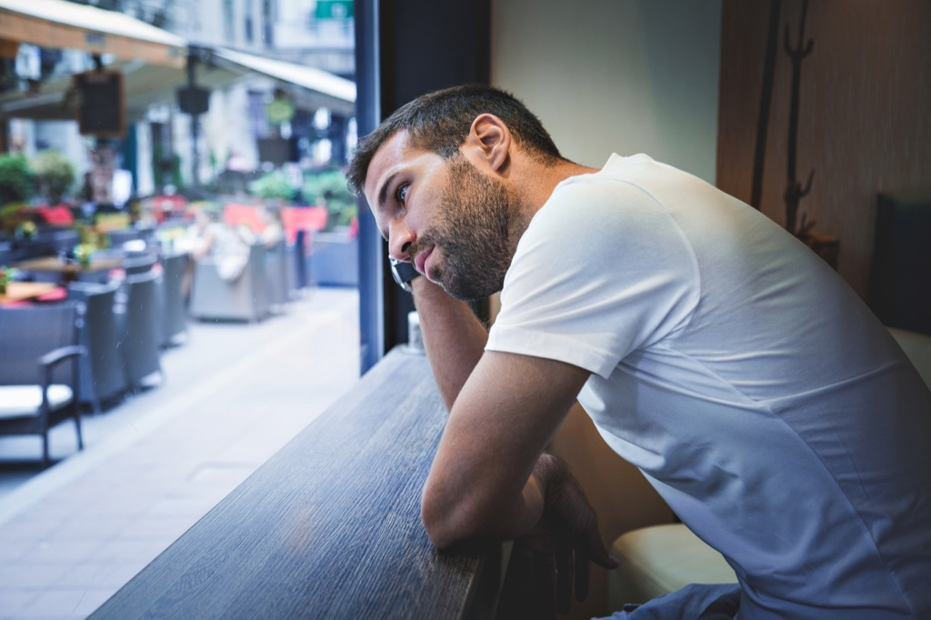white man thinking while he leans on counter at cafe