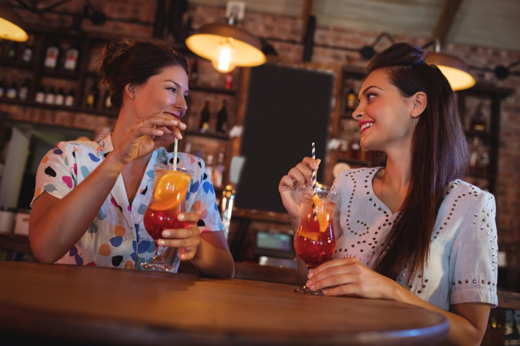 two women having drinks together at a bar, how to make friends as an adult