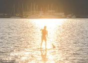 Man paddleboarding in Seattle, one of the healthiest cities in America.