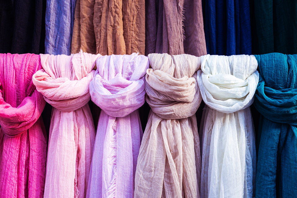 pink and purple scarves hanging on a rack - how to dress over 50