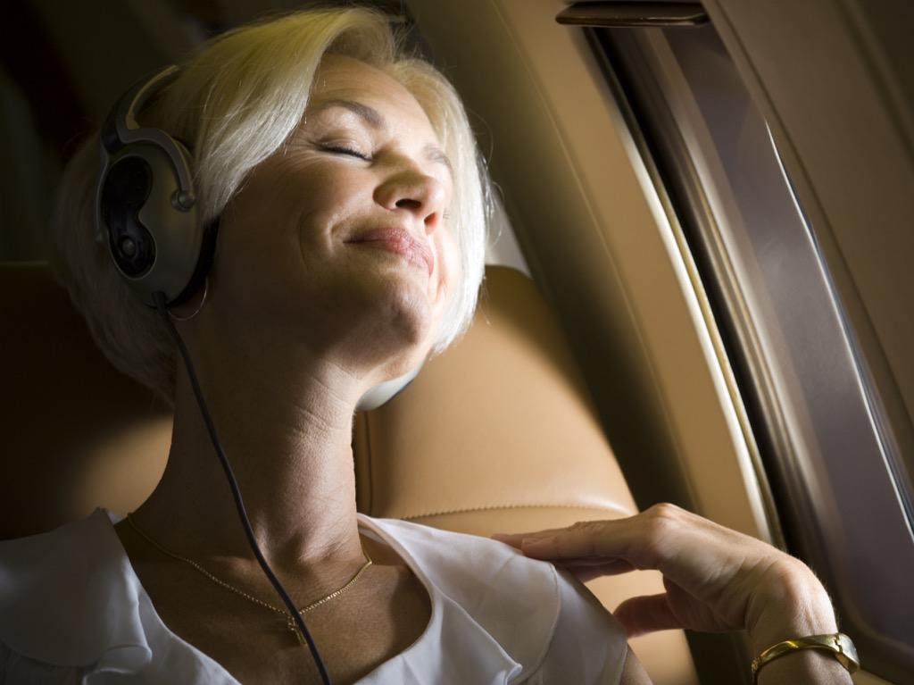older woman sleeping on airplane