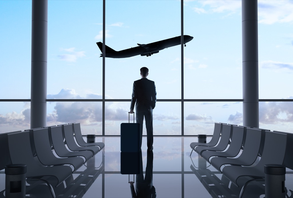 man stands in an airport gate watching a plane take off