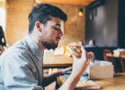 millennial eating burger ways we're unhealthy