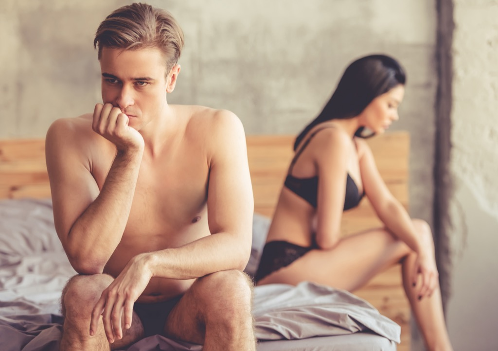 couple on bed looking upset, ways your body changes after 40