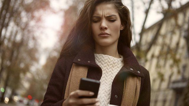woman checking phone surprised shocked