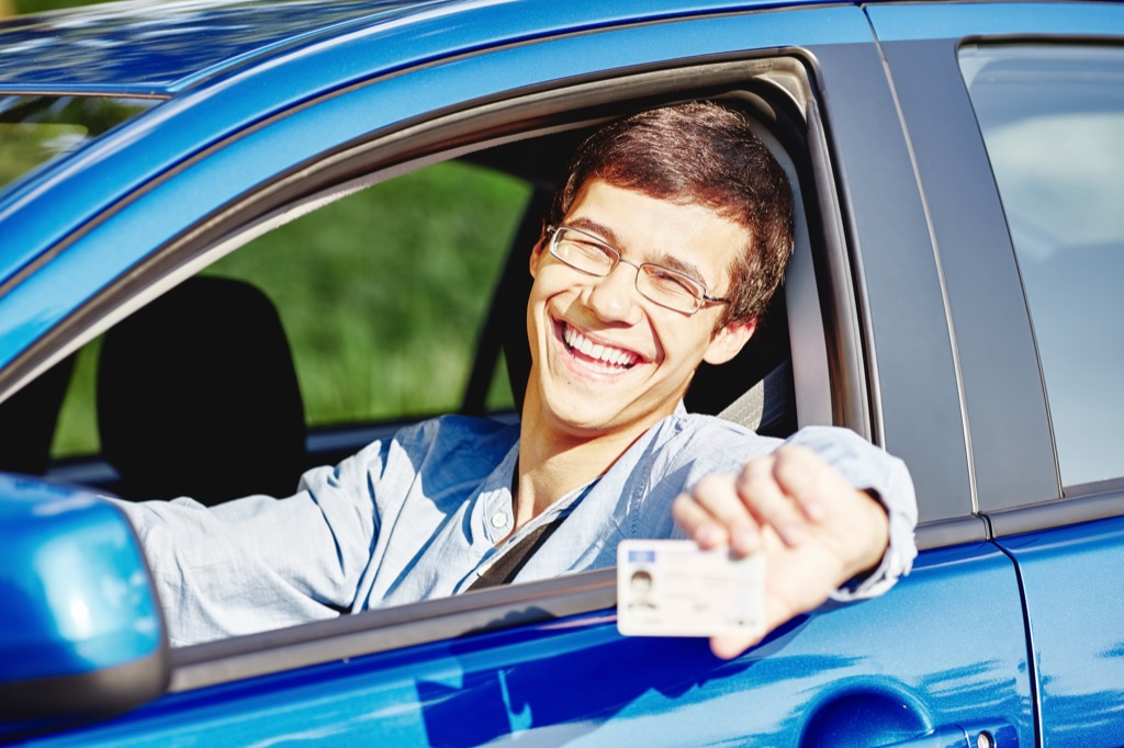 Young man sitting in a car and holding up his driver's license