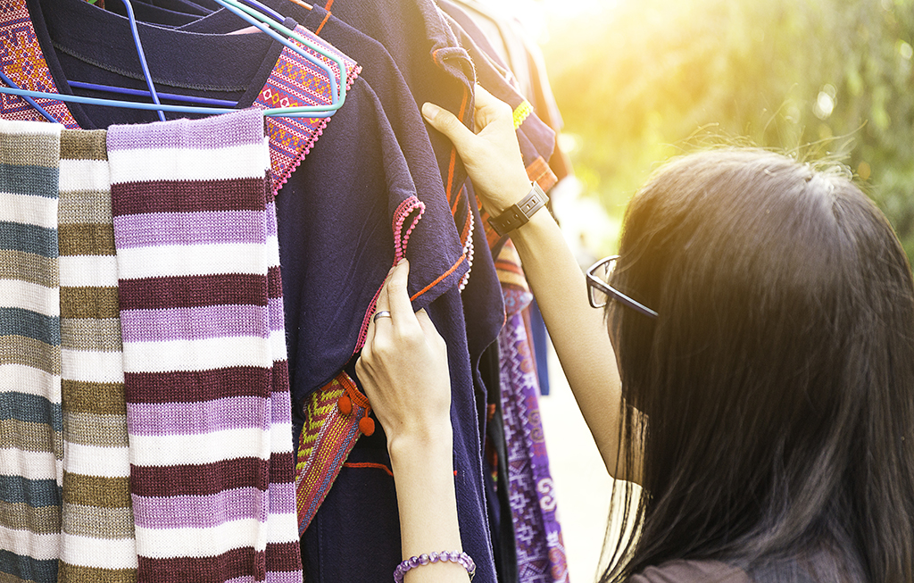 woman looking at a rack of clothes outside - how to dress over 50