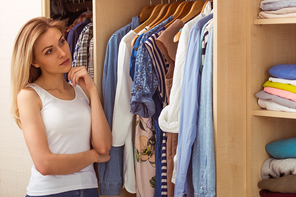 Woman looking at clothes in closet housekeeper secrets
