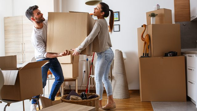young couple moving boxes into new house, living together before marriage
