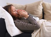 woman sneezing sick on the couch