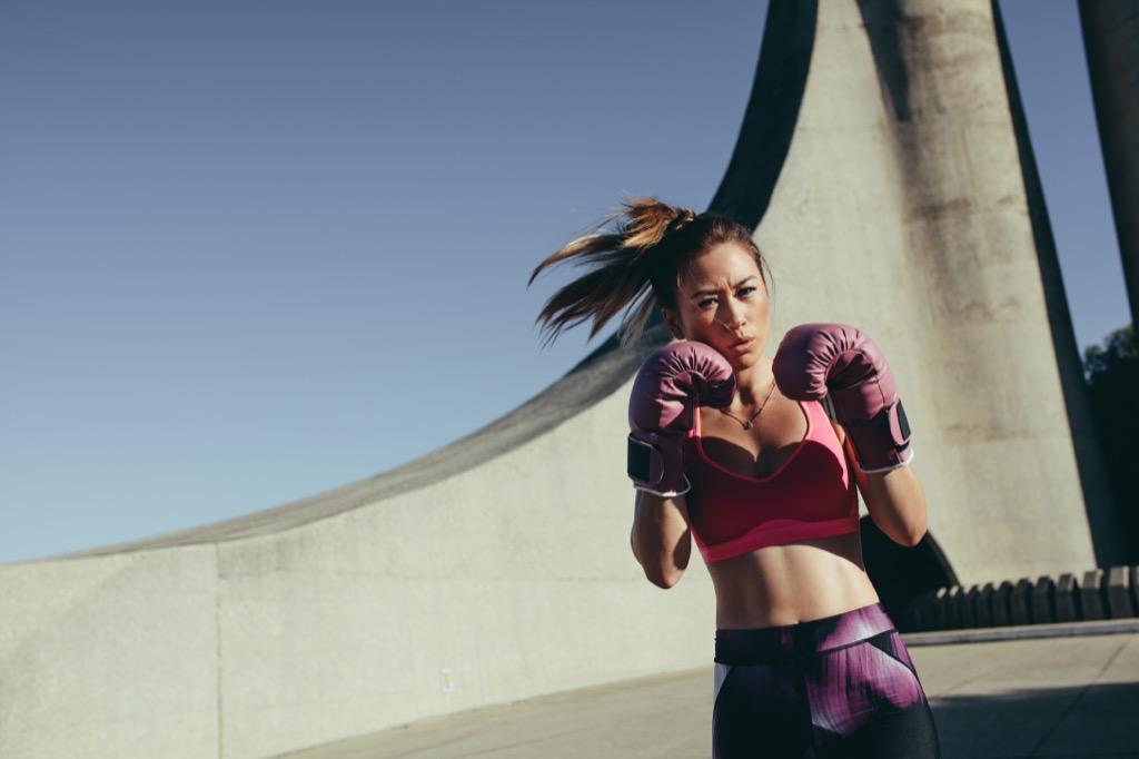Woman kickboxing, strip away stress
