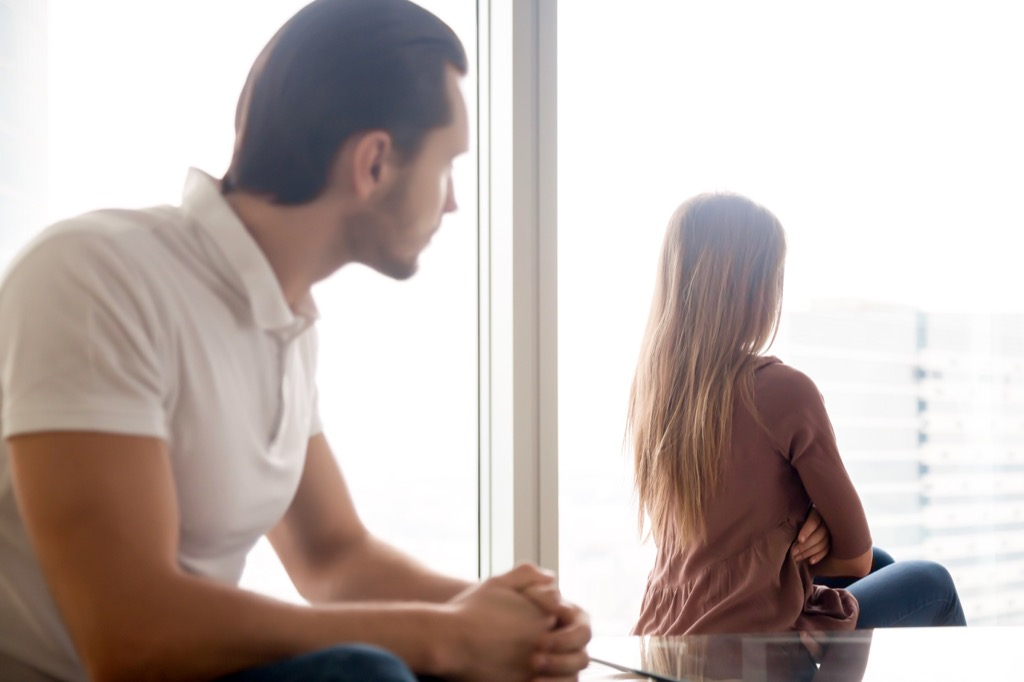 upset woman looking out the window with man who needs to apologize, signs of cheating
