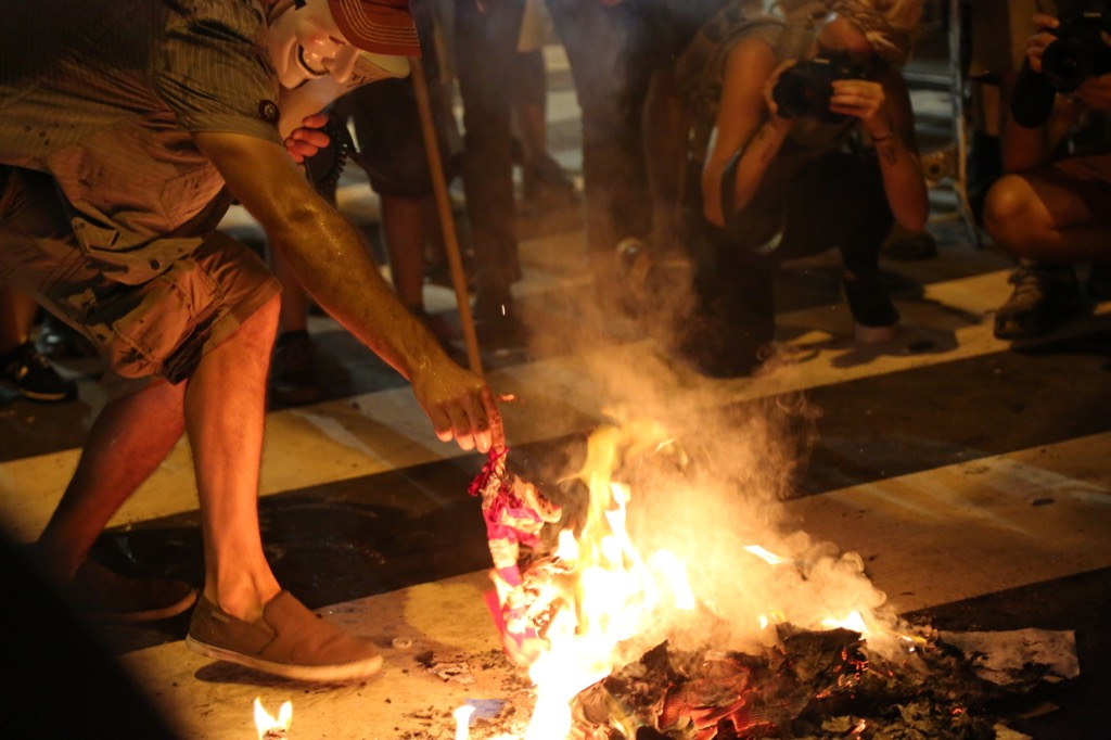 a man burning the american flag outside the 2016 democratic convention