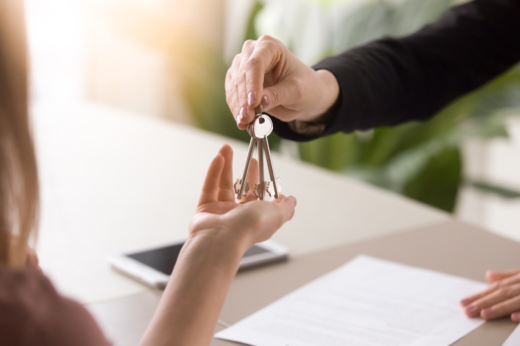 woman handing keys to another woman, downsizing your home