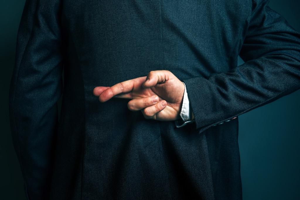 dishonest man crossing fingers commit