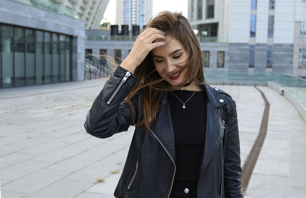 woman fixing hair - how to tell if a girl is playing hard to get