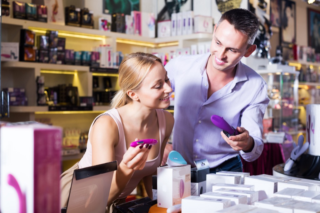 man and woman shopping for sex toys in a shop